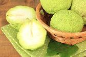 Osage Orange fruits (Maclura pomifera) in basket, on wooden background — Photo