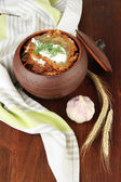 Potato pancakes in pot, on wooden background — Stockfoto