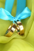 Wedding rings tied with ribbon on bright fabric — Stock Photo