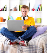 Young man relaxing on sofa with laptop — 图库照片