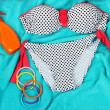 Swimsuit and beach items on bright blue background — Stock Photo #32340349