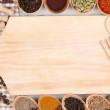 Various spices and herbs with empty wooden board — Stock Photo #32341623