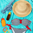 Swimsuit and beach items on bright blue background — Stock Photo #32342369