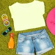 Top, shorts and beach items on bright green background — Stock Photo #32342461