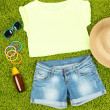 Top, shorts and beach items on bright green background — Stock Photo #32342993