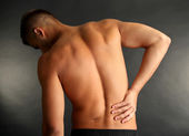 Young man with back pain on grey background — Stock Photo