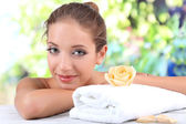 Beautiful girl with spa accessories on natural background — Stok fotoğraf