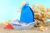 在沙子上,蓝色背景上的蓝色玩具船 — 图库照片