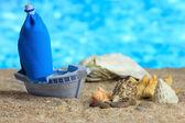 Blue toy ship on sand, on blue background — Stock Photo