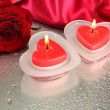 Beautiful candles, rose and red silk on grey wet background — Stock Photo #32501543
