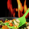 Casserole with vegetables and meat on pan, on fire background — Stock Photo #32501707