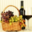 Ripe grapes in wicker basket, bottle and glass of wine, on light background — 图库照片