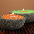 Candles in stone bowls with marine salt, on bamboo mat, on brown background — Stock Photo