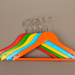 Colorful clothes hangers on gray background — Stock Photo
