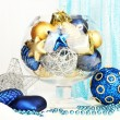 Christmas decorations in glass vase on fabric background — Stock Photo