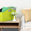Magazines and folders in green box on bedside table in room — Stock Photo #32505097