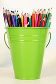 Color bucket with multicolor pencils, on color background — Stock Photo