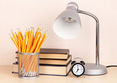 Table lamp with books on desk in room — Stock Photo