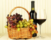 Ripe grapes in wicker basket, bottle and glass of wine, on light background — Стоковое фото