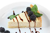 Slice of cheesecake with chocolate sauce and blackberry on plate, isolated on white — Stock Photo