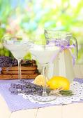 Limonata lavanda in caraffa di vetro e bicchieri da cocktail, su sfondo luminoso — Foto Stock