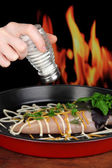 Hand adding spices to raw chicken fillets on dripping pan, on fire background — Stock Photo