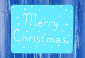 Signboard with words Merry Christmas on blue wooden table background close-up — Stock Photo
