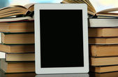 Tablet and books on light background — Stock Photo