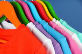 Different shirts on colorful hangers on blue background — Stok fotoğraf