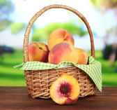 Ripe sweet peaches in wicker basket, on bright background — Foto Stock