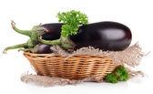 Frische auberginen in weidenkorb isoliert auf weiss — Stockfoto