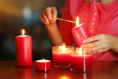 Woman lights candles on bright background — Stock Photo