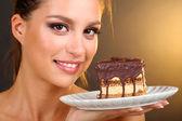 Ritratto di ragazza giovane e bella con cupcake al cioccolato su sfondo marrone — Foto Stock
