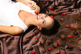 Woman lying on brown atlas covered by chocolate and candies — Stock Photo