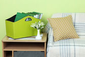 Magazines and folders in green box on bedside table in room — Stock Photo