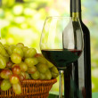 Ripe grapes in wicker basket, bottle and glass of wine, on bright background — Stock Photo #32560985