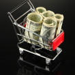 Shopping trolley with dollars, on dark background — Stock Photo #32561413