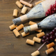 Old bottles of wine, grapes and corks on wooden background — Stock Photo #32561895