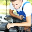 Young auto mechanic repairing car engine outdoors — Stock Photo #32562159