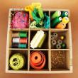 Thread and sewing tools in box on brown background — 图库照片