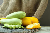 Sliced and whole raw zucchini on burlap background — Stock Photo