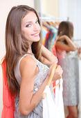 Beautiful girl with dresses near mirror — Stockfoto