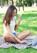 在公园的笔记本电脑的漂亮年轻女孩 — 图库照片