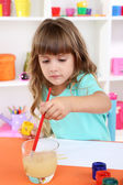 Little girl draws sitting at table in room on shelves background — Foto Stock