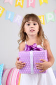 Petite fille avec cadeau en chambre sur fond de mur gris — Photo