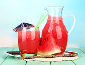 Glass of fresh watermelon juice, on wooden table, on bright background — Stock Photo