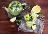 Tetera y taza de té con jengibre en cilicio sobre mesa de madera — Foto de Stock