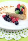 Fetta di cheesecake con lamponi e blackberry su piastra, su fondo in legno — Foto Stock