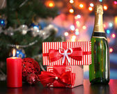 Many gifts and bottle of champagne on bright background — Stok fotoğraf