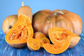 Ripe cut pumpkins on wooden table on blue background — Stock Photo